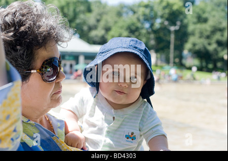 Hispanic woman holds her six month old grandson near the Frog Pond in Boston Common, Boston MA - Stock Photo