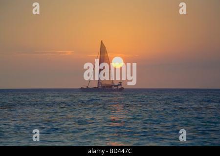 Sailboat against the sunrise, Roatan Island, Honduras - Stock Photo