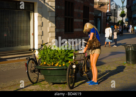 Young woman locking her bicycle while talking on a mobile phone in Gamla Staden Malmö Skåne Sweden Europe - Stock Photo