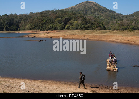 India Kerala Periyar national park tourist guide and eco tourists being ferried on bamboo raft - Stock Photo