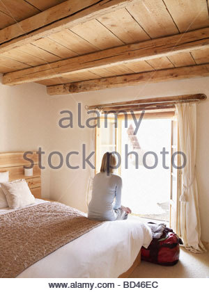 woman sitting on bed - Stock Photo