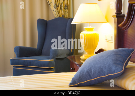 Detail of a luxury hotel bedroom featuring bed, chair and bedside lamp - Stock Photo