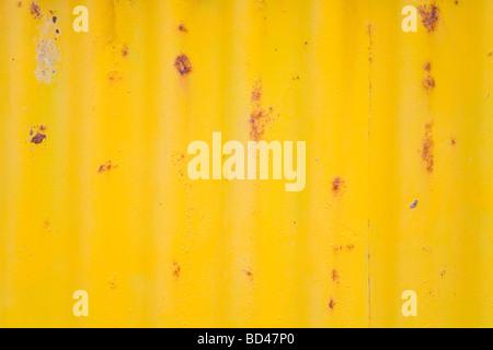Rusty corrugated iron closeup with peeling yellow paint