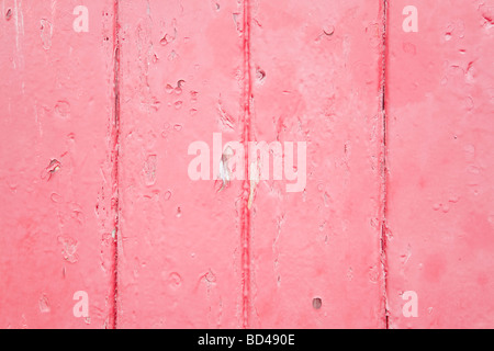 Closeup of wood panels with peeling pink paint - Stock Photo