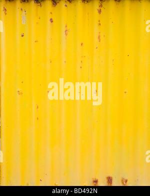 Rusty corrugated iron with peeling yellow paint - Stock Photo
