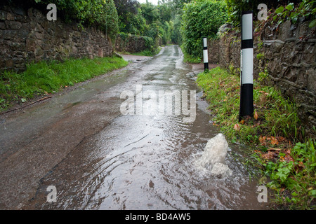 Water gushing out of drain and water running down country lane after heavy rainfall. - Stock Photo