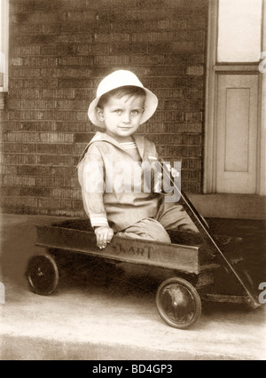 Little Boy in Sailor Suit in a Wagon - Stock Photo