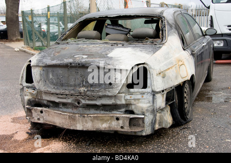 rear of burnt out stolen saloon car - Stock Photo