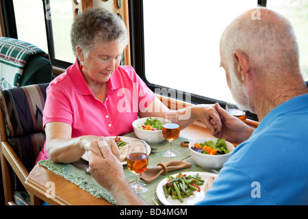 Senior couple says a prayer over a healthy turkey dinner served in the kitchen of their mobile home - Stock Photo
