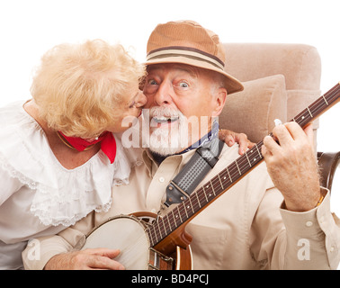 Senior man playing banjo for his lady is rewarded with a kiss  - Stock Photo
