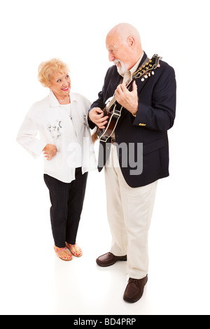 Handsome senior man serenading his beautiful lady on the mandolin Full body isolated  - Stock Photo