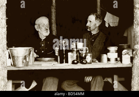 Two Old Timers Dining in Crude Shack - Stock Photo