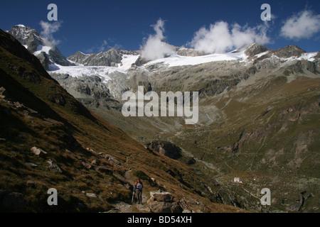 Female Hiker walking above hotel du Trift Zermatt Valais Switzerland - Stock Photo