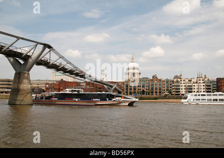 Tourist boats pass under the Millennium Bridge close to St Pauls Cathedral. View: south bank of the River Thames, - Stock Photo