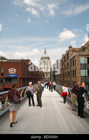 Londoners and vistors mix on the Millennium Bridge with St Pauls Cathedral behind. - Stock Photo