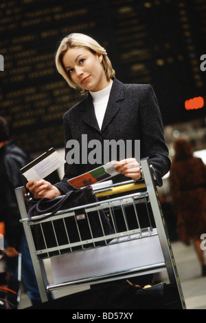 Woman standing with luggage cart in train station holding travel ticket looking away - Stock Photo