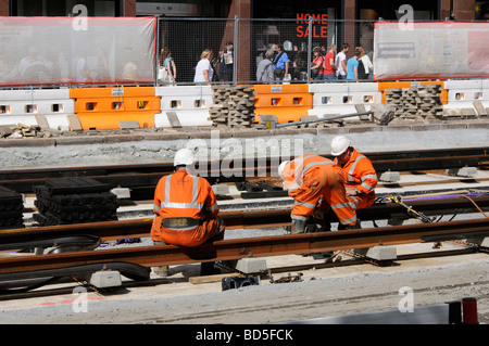 Men working on the tram tracks on Princes Street, Edinburgh, Scotland, UK. - Stock Photo