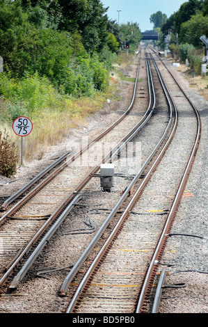Royalty free photograph of railway tracks with speed limit sign and live rail in London UK - Stock Photo