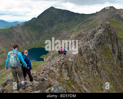 Walking along the knife edge ridge between Crib Goch and Mount Snowdon, North Wales. - Stock Photo