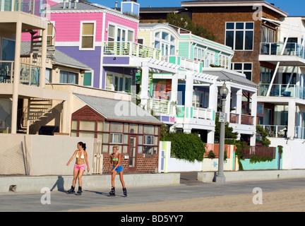 Roller bladers skate past beach front homes - Stock Photo