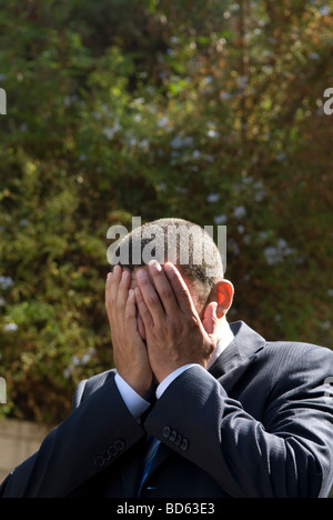 Business man head in hands outdoors - Stock Photo
