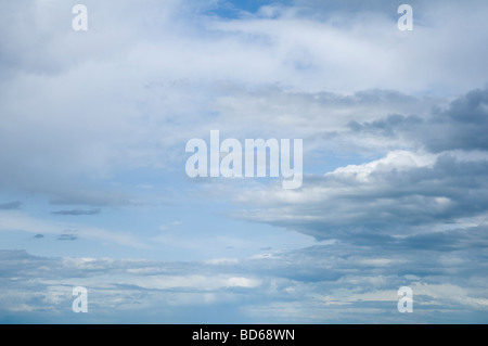 Soft misty cumulus and grey stratus Clouds, with a blue sky beyond. - Stock Photo