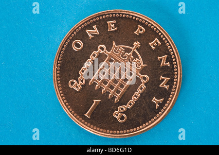 Shiny new one penny coin against a blue background - Stock Photo