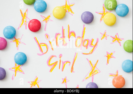 Birthday girl, stars and smarties written in coloured pencils on paper - Stock Photo