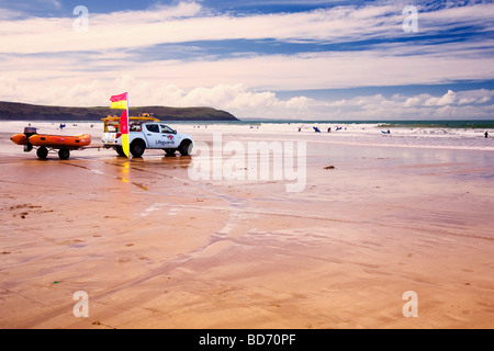 RNLI (Royal National Lifeboat Institution) Lifeguards with 4x4 and dinghy patrol the sands on Woolacombe beach in - Stock Photo