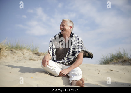 Male Best Ager sitting in the dunes at the North Sea in De Haan, Belgium, Europe - Stock Photo