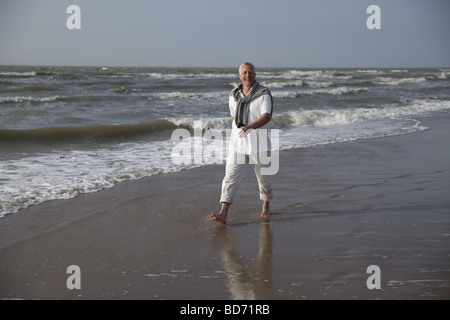 Male Best Ager walking on the beach of the North Sea in De Haan, Belgium, Europe - Stock Photo