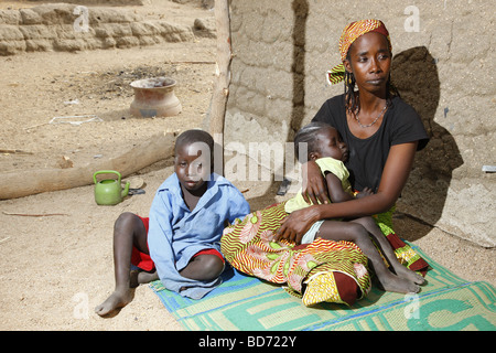 Woman and her two children seated in front of a house, Maroua, Cameroon, Africa - Stock Photo