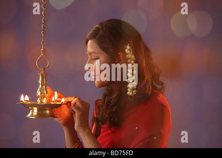 Hindu devotee lights earthen lamps as she celebrate Hindus Devali Festival Diwali known as the Festival of Lights - Stock Photo
