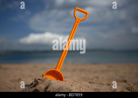 childs toy plastic spade stuck into the sand on a beach in the uk - Stock Photo