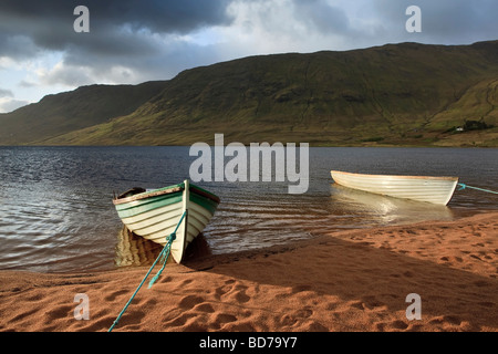 Two Rowing boat used for angling tied up on the banks of an Irish lake in the Galway Mayo region of Ireland - Stock Photo