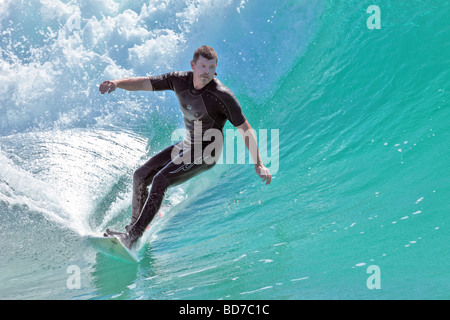 Surfer captures a wave for a ride into the shore late afternoon - Stock Photo