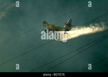 Canadian Bombadier superscooper aircraft dropping water on forest fire on the Costa del Sol, Andalucia, Spain - Stock Photo