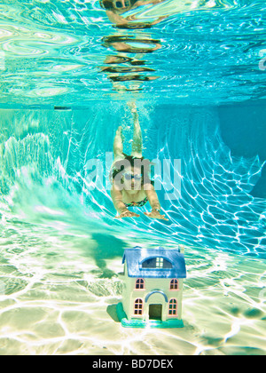 Woman diving after sinking house - Stock Photo