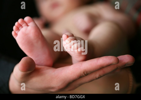 Father holding his child's feet - Stock Photo