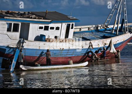 Indonesia Sulawesi Tanah Beru near Pantai Bira Bira Beach traditional wooden boat building men repairing boat - Stock Photo