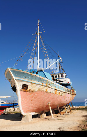 Fishing boat or trawler undergoing maintenance in a dry dock in Latchi, Paphos, Greece - Stock Photo