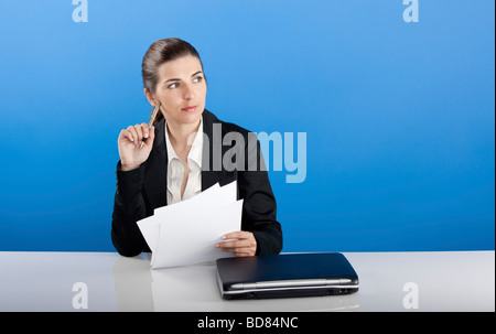 Businesswoman sitting in office thinking in something - Stock Photo