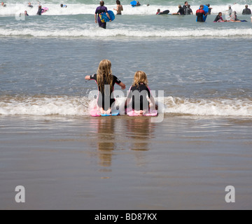 Two young girls playing in waves - Stock Photo