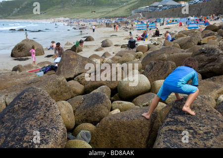 A six year old boy climbs on the rocks at Sennen Cove, Cornwall, UK - Stock Photo