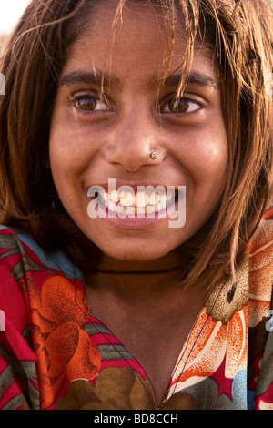 Young Smiling Indian Girl with Colourful Flowery dress, Thar Desert, Near Jaisalmer, Rajasthan State, India. - Stock Photo