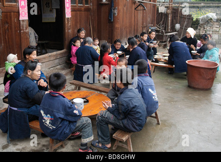 Dong women and children eating at wedding feast Chejing village Guizhou Province China - Stock Photo