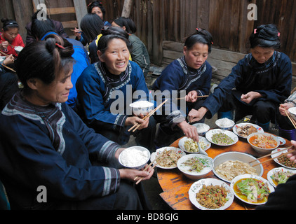 Dong women eating at wedding feast Chejing village Guizhou Province China - Stock Photo