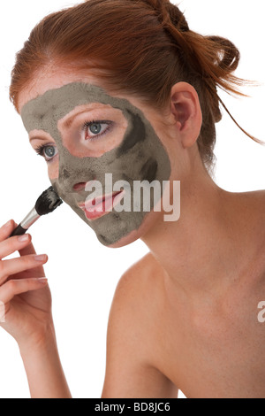 Body care - Young woman with mud mask on white background - Stock Photo