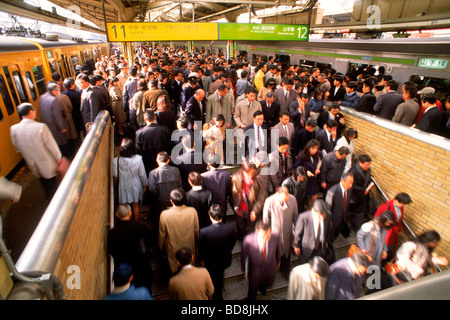 Commuter traffic entering and leaving in motion at city subway station in Tokyo - Stock Photo