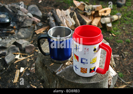 Two drinking cups on a log in the Willmore Wilderness Park Canada - Stock Photo